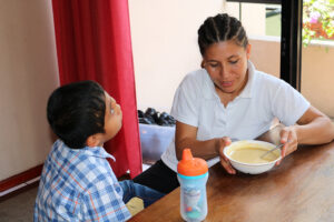A special mother helps Miguel learn to feed himself.