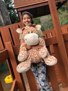 Yohana with a stuffed giraffe